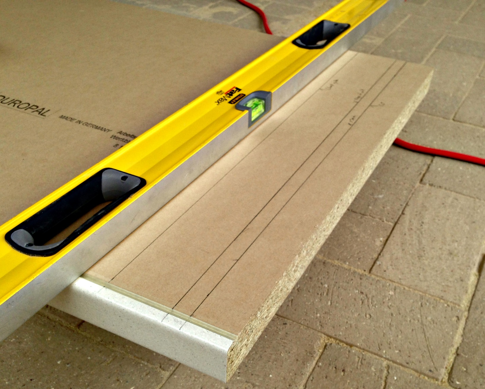 Spirit level clamped to worktop as a straight edge